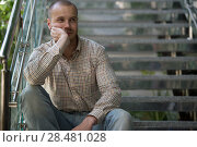 Portrait of handsome confident young businessman sitting on stairs at modern office building. Стоковое фото, фотограф Kirill Kedrinskiy / Ingram Publishing / Фотобанк Лори