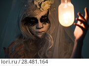 Купить «Halloween witch. Beautiful woman wearing santa muerte mask casting spell near light bulb», фото № 28481164, снято 21 сентября 2014 г. (c) Ingram Publishing / Фотобанк Лори