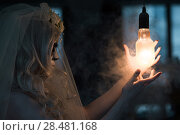 Halloween witch. Beautiful woman wearing santa muerte mask casting spell near light bulb. Стоковое фото, фотограф Kirill Kedrinskiy / Ingram Publishing / Фотобанк Лори