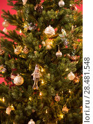 Купить «Christmas Tree on red background decorated with golden balls toys and bows», фото № 28481548, снято 3 ноября 2014 г. (c) Ingram Publishing / Фотобанк Лори