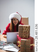 Купить «Young pretty woman wearing Santa Claus hat wrapping Christmas gift at her desk and responding to children messages and wishes by email», фото № 28481636, снято 12 ноября 2014 г. (c) Ingram Publishing / Фотобанк Лори