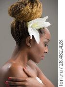 Купить «Portrait of a sensual young African woman with lily flower in hair», фото № 28482428, снято 20 ноября 2014 г. (c) Ingram Publishing / Фотобанк Лори