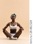 Купить «Young African woman in the lotus meditation position doing yoga», фото № 28482524, снято 20 ноября 2014 г. (c) Ingram Publishing / Фотобанк Лори