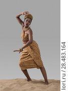 Купить «Attractive young African fashion model standing on sand on gray studio background», фото № 28483164, снято 1 декабря 2014 г. (c) Ingram Publishing / Фотобанк Лори