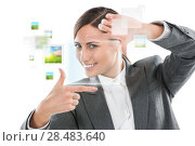 Купить «Portrait of beautiful business woman making frame gesture on white background and virtual pictures surrounding her», фото № 28483640, снято 2 февраля 2013 г. (c) Ingram Publishing / Фотобанк Лори