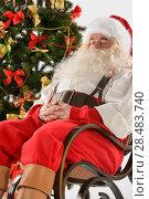 Santa Claus sitting in rocking chair near Christmas Tree at home and sleeping. Стоковое фото, фотограф Kirill Kedrinskiy / Ingram Publishing / Фотобанк Лори