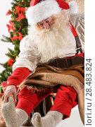 Santa Claus sitting in rocking chair near Christmas Tree at home and massages his foot. Стоковое фото, фотограф Kirill Kedrinskiy / Ingram Publishing / Фотобанк Лори