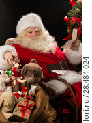 Купить «Santa Claus sitting at home at comfortable armchair holding envelope and reading children's letters and wishes and choosing toys from big sack near him», фото № 28484024, снято 12 января 2013 г. (c) Ingram Publishing / Фотобанк Лори