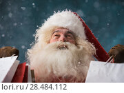 Купить «Photo of happy Santa Claus outdoors in snowfall holding shopping bags. Christmas sales and discount concept», фото № 28484112, снято 25 сентября 2013 г. (c) Ingram Publishing / Фотобанк Лори