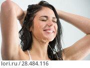 Купить «Woman washing her head while showering with happy smile and water splashing. Beautiful Caucasian female model home in shower cabin.», фото № 28484116, снято 7 мая 2013 г. (c) Ingram Publishing / Фотобанк Лори