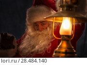 Купить «Santa Clause walking outdoors under falling snow with vintage lamp», фото № 28484140, снято 25 сентября 2013 г. (c) Ingram Publishing / Фотобанк Лори