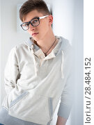 Купить «Portrait of young fashionable man leaning on white wall and wearing glasses. He is trendy fashionable or maybe gay», фото № 28484152, снято 13 апреля 2013 г. (c) Ingram Publishing / Фотобанк Лори