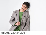 Купить «Happy smiling young man leaning against white wall with copy space an the right», фото № 28484224, снято 13 апреля 2013 г. (c) Ingram Publishing / Фотобанк Лори