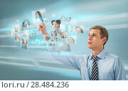 Купить «Portrait of young businessman choosing people for his business team using virtual computer interface», фото № 28484236, снято 23 февраля 2013 г. (c) Ingram Publishing / Фотобанк Лори