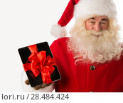 Купить «Portrait of happy Santa Claus holding gift Tablet computer in his hands with ribbon and looking at camera», фото № 28484424, снято 19 января 2013 г. (c) Ingram Publishing / Фотобанк Лори