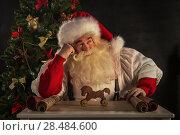 Купить «Santa Claus working - preparing and wrapping christmas gifts, toys before sending it to children», фото № 28484600, снято 31 января 2013 г. (c) Ingram Publishing / Фотобанк Лори