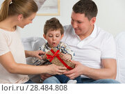 Купить «Couple giving gift to their little son in the living room. Happy family portrait», фото № 28484808, снято 31 марта 2013 г. (c) Ingram Publishing / Фотобанк Лори