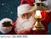 Купить «Santa Claus is holding a shining lantern while sneaking to his home outdoors at North Pole», фото № 28484900, снято 25 сентября 2013 г. (c) Ingram Publishing / Фотобанк Лори