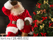 Купить «Santa Claus decorating Christmas tree in dark room», фото № 28485032, снято 31 января 2013 г. (c) Ingram Publishing / Фотобанк Лори