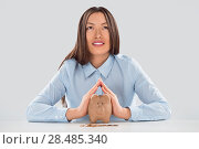 Купить «Happy business woman covering piggy bank with two hands - safety for your money concept», фото № 28485340, снято 2 февраля 2013 г. (c) Ingram Publishing / Фотобанк Лори