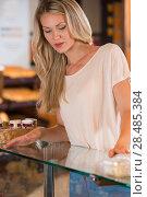 Купить «Pretty lady in the store looking at showcase», фото № 28485384, снято 16 июля 2013 г. (c) Ingram Publishing / Фотобанк Лори