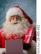 Купить «Happy Santa Claus opening his Christmas gift at North Pole», фото № 28485432, снято 25 сентября 2013 г. (c) Ingram Publishing / Фотобанк Лори