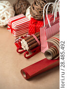 Купить «Christmas background with red and natural decorations, gift boxes, little bags with presents», фото № 28485492, снято 3 ноября 2012 г. (c) Ingram Publishing / Фотобанк Лори