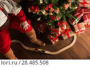 Купить «Unrecognizable Santa Claus playing with wooden railroad near Christmas tree. Top view indoors at dark room», фото № 28485508, снято 31 января 2013 г. (c) Ingram Publishing / Фотобанк Лори