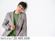Купить «Serious young man leaning against white wall with copy space an the right», фото № 28485608, снято 13 апреля 2013 г. (c) Ingram Publishing / Фотобанк Лори