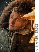 Brutal man walking under snowstorm at night lighting his way with lantern. Стоковое фото, фотограф Kirill Kedrinskiy / Ingram Publishing / Фотобанк Лори