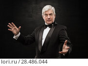 Купить «Portrait of professional hypnotist on black background», фото № 28486044, снято 28 января 2013 г. (c) Ingram Publishing / Фотобанк Лори