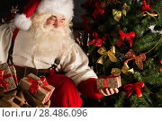 Купить «Santa putting gifts under Christmas tree in dark room», фото № 28486096, снято 31 января 2013 г. (c) Ingram Publishing / Фотобанк Лори