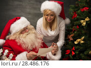 Portrait of happy Santa Claus sitting at his room at home with his woman helper near Christmas tree and big sack and reading Christmas letter or wish list. Стоковое фото, фотограф Kirill Kedrinskiy / Ingram Publishing / Фотобанк Лори