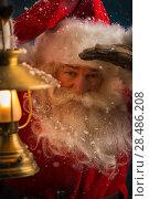 Купить «Santa Clause walking outdoors under falling snow with vintage lamp», фото № 28486208, снято 25 сентября 2013 г. (c) Ingram Publishing / Фотобанк Лори