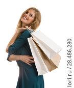 Young girl wearing elegant dress posing against white background. Holding shopping bags and looking upwards. Стоковое фото, фотограф Kirill Kedrinskiy / Ingram Publishing / Фотобанк Лори