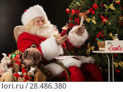 Купить «Santa Claus sitting at home at comfortable armchair holding envelope and reading children's letters and wishes and choosing toys from big sack near him», фото № 28486380, снято 12 января 2013 г. (c) Ingram Publishing / Фотобанк Лори