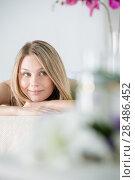 Купить «Woman on spa or massage with flowers and cosmetics on foreground making perfect copyspace», фото № 28486452, снято 7 мая 2013 г. (c) Ingram Publishing / Фотобанк Лори