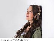 Купить «Portrait of a mixed race college student at campus leaning wall and listening music with cool headphones», фото № 28486540, снято 13 апреля 2013 г. (c) Ingram Publishing / Фотобанк Лори