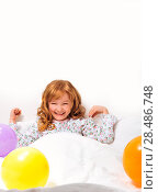 Smiley little girl in bed surrounded by coloured ballon. Стоковое фото, агентство Ingram Publishing / Фотобанк Лори