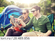 Купить «happy couple with tablet pc at camping tent», фото № 28489856, снято 27 мая 2016 г. (c) Syda Productions / Фотобанк Лори