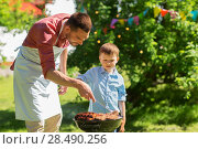Купить «father and son cooking meat on barbecue grill», фото № 28490256, снято 9 июля 2017 г. (c) Syda Productions / Фотобанк Лори