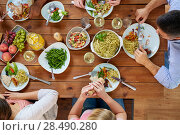 Купить «group of people eating at table with food», фото № 28490280, снято 5 октября 2017 г. (c) Syda Productions / Фотобанк Лори