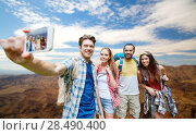 Купить «friends with backpack taking selfie by smartphone», фото № 28490400, снято 25 июля 2015 г. (c) Syda Productions / Фотобанк Лори