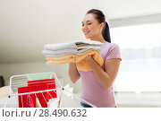 Купить «woman with bath towels and drying rack at home», фото № 28490632, снято 29 апреля 2018 г. (c) Syda Productions / Фотобанк Лори