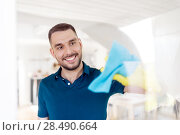 Купить «man in rubber gloves cleaning window with rag», фото № 28490664, снято 10 мая 2018 г. (c) Syda Productions / Фотобанк Лори