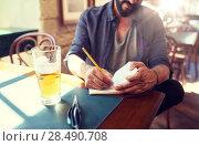 Купить «close up of man with beer and notebook at pub», фото № 28490708, снято 2 июня 2016 г. (c) Syda Productions / Фотобанк Лори