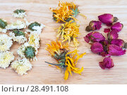Купить «Dried flowers of white chrysanthemum, orange calendula and buds of pink rose for green herbal tea on a wooden table», фото № 28491108, снято 20 апреля 2018 г. (c) Виктория Катьянова / Фотобанк Лори