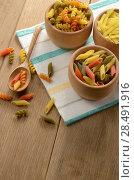 Купить «Raw tricolor pasta set on the wooden table», фото № 28491916, снято 13 января 2013 г. (c) Ingram Publishing / Фотобанк Лори