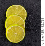 Купить «Fresh lima slices with water drops on black slate stone background», фото № 28492728, снято 18 июля 2019 г. (c) Ingram Publishing / Фотобанк Лори