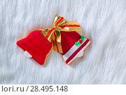 Купить «Christmas cookies Xmas red bell shape and ribbon on white fur background», фото № 28495148, снято 8 декабря 2013 г. (c) Ingram Publishing / Фотобанк Лори